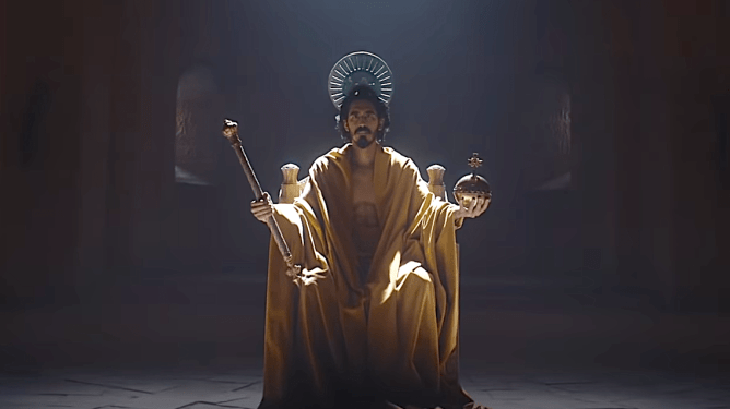 Dev Patel wearing golden robes while sitting on a throne as seen in The Green Knight, a film with a 2021 release date from A24.