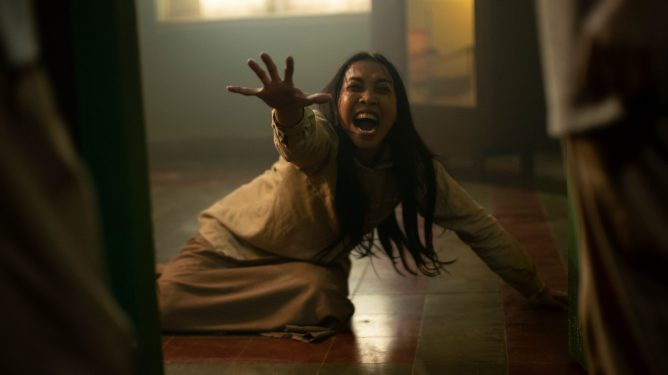 A woman shrieks in terror as she reaches out for help as seen in The Queen of Black Magic.