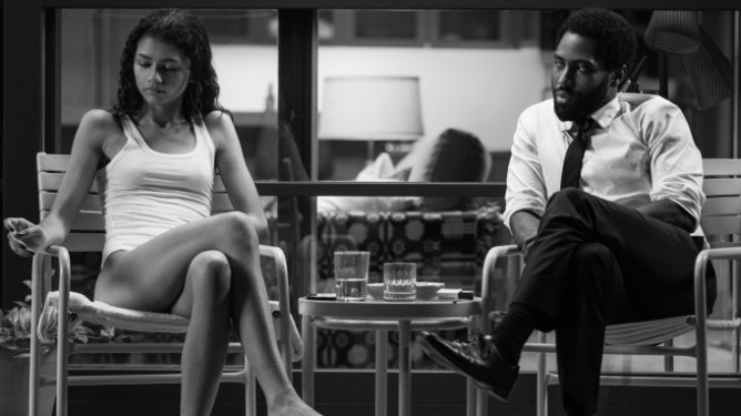 Zendaya and John David Washington share a tense moment as they sit on their modern patio as seen in the black-and-white film Malcolm & Marie.