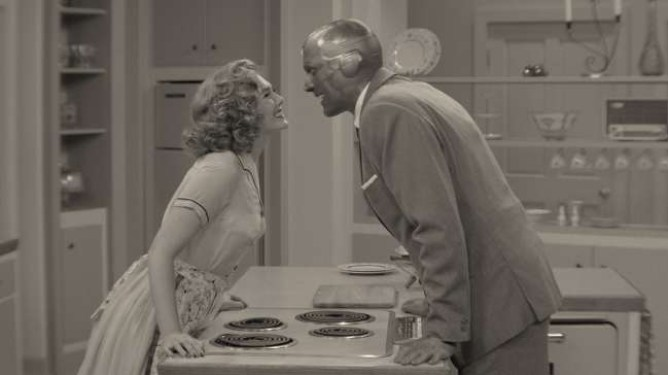 Paul Bettany and Elizabeth Olsen lean in for a kiss as the two settle into their new kitchen in a 50s inspired black and white setting as seen in WandaVision.
