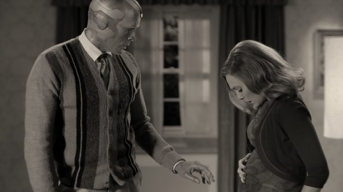 Paul Bettany as the Vision examines the pregnant belly of Elizabeth Olsen as Wanda Maximoff as the two stand in their 50s inspired black and white living room.