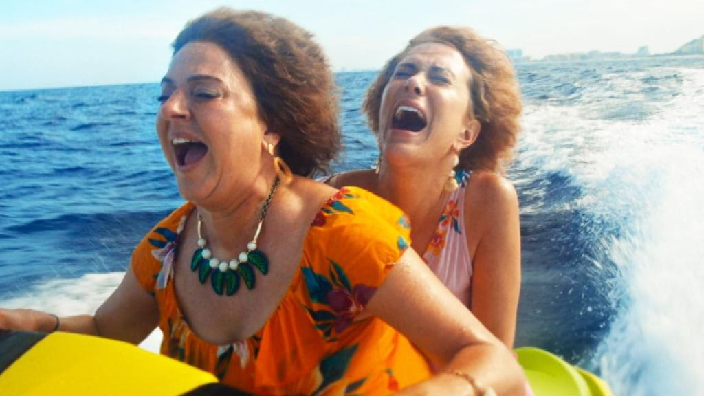 Kristen Wiig and Annie Mumolo riding a fast jet ski as seen in Barb and Star Go to Vista Del Mar directed by Josh Greenbaum.