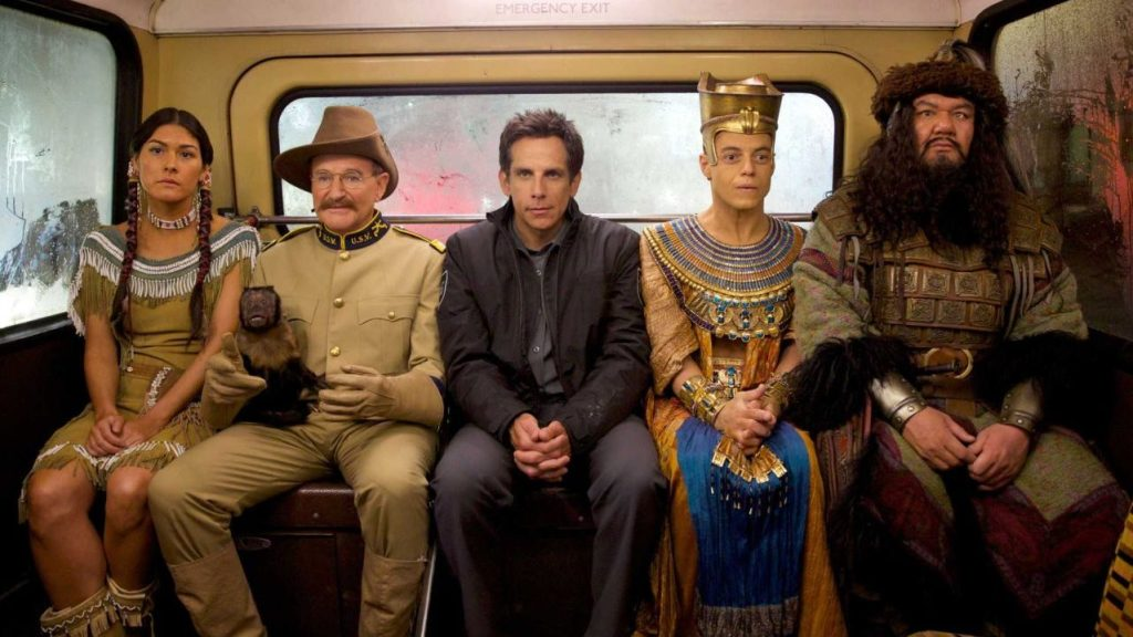 Larry Daley (Ben Stiller), Teddy Roosevelt (Robin Williams), Ahkmenrah (Rami Malek), Sacagawea (Mizuo Peck), and Atilla the Hun (Patrick Gallagher) sitting at the back of a bus in Night at the Museum: Secret of the Tomb.