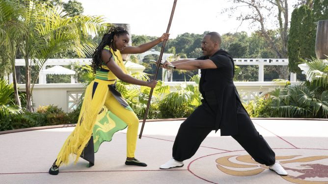 KiKi Layne and Eddie Murphy practicing bow staff combat as seen in Coming 2 America on Prime Video.