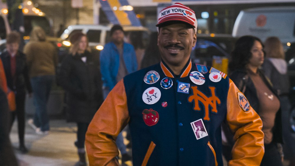 Eddie Murphy smiling and wearing a New York Mets jacket and tourist clothes as seen in Coming 2 America.