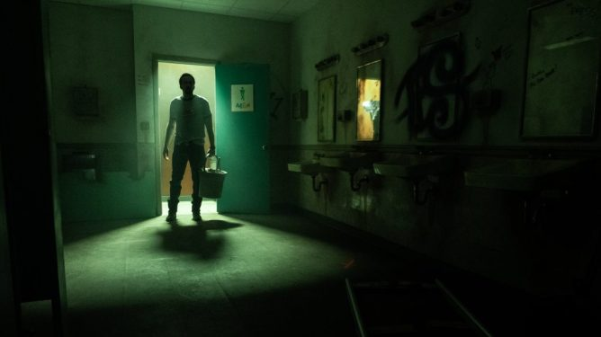 Nicolas Cage as the Janitor entering a dark and scary bathroom as seen in Willy's Wonderland directed by Kevin Lewis.