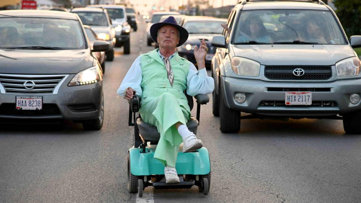 Udo Kier wearing a colorful suit while driving a wheel chair as seen in the SXSW film Swan Song.