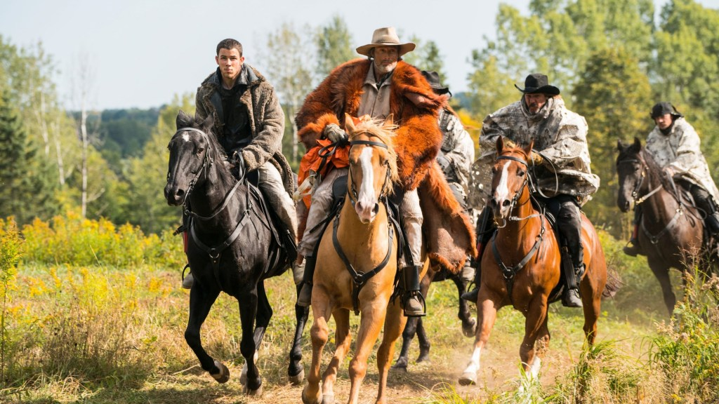 Nick Jonas and Mads Mikkelsen riding horses in action as seen in Chaos Walking.