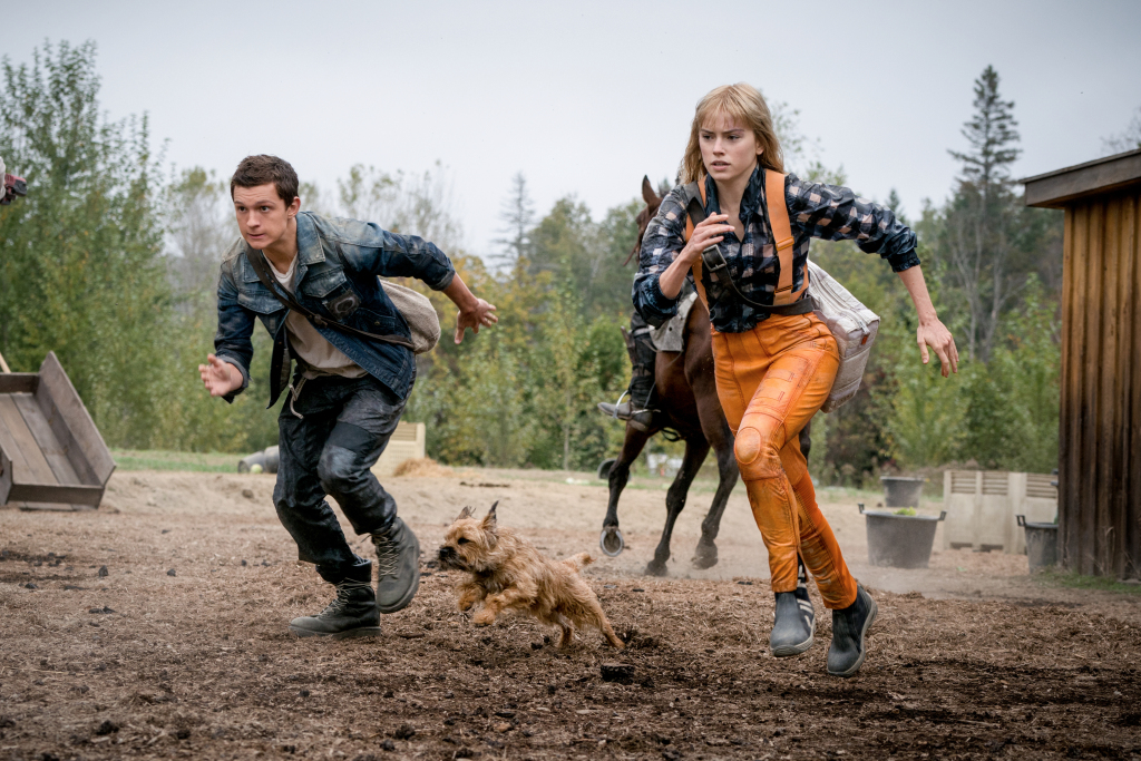 Tom Holland and Daisy Ridley and a small dog in action as seen in Chaos Walking.
