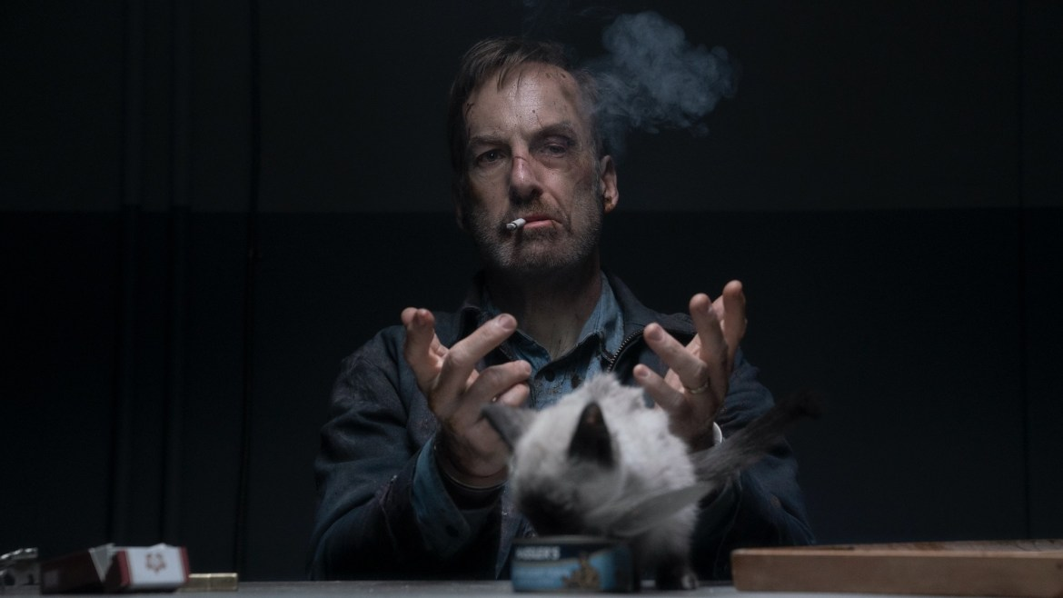 Bob Odenkirk looking beat up while smoking in front of a cat as seen in the action comedy Nobody.