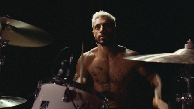 Riz Ahmed playing drums shirtless as seen in the Oscar nominated film Sound of Metal.