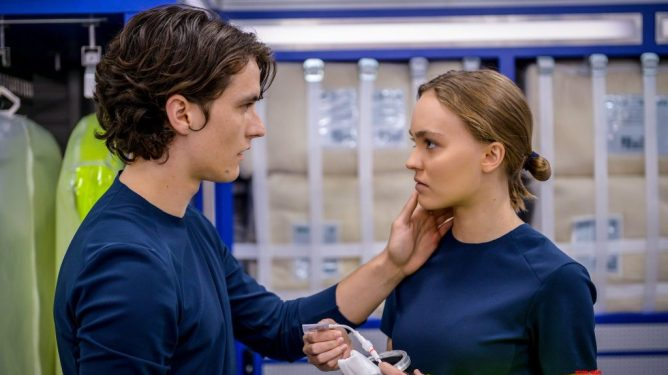 Fionn Whitehead holding Lily-Rose Depp's face in a futuristic space ship as seen in Voyagers.
