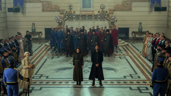 Jessie Mei Li as Alina Starkov and Ben Barnes as General Kirigan in the center of a palace crowd as seen in the new Netflix series Shadow and Bone.