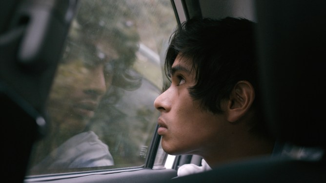 Jose Angeles as Nito looking out the window of a moving car as seen in the new youth drama Beast Beast.