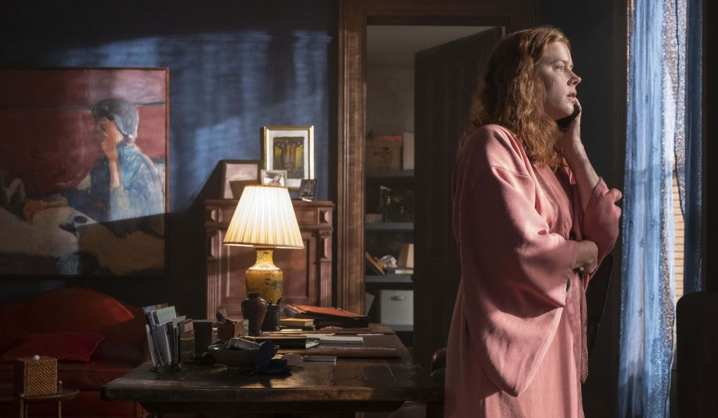 Amy Adams calling the police from inside her house as she spies on neighbors as seen in the new Netflix film The Woman in the Window.