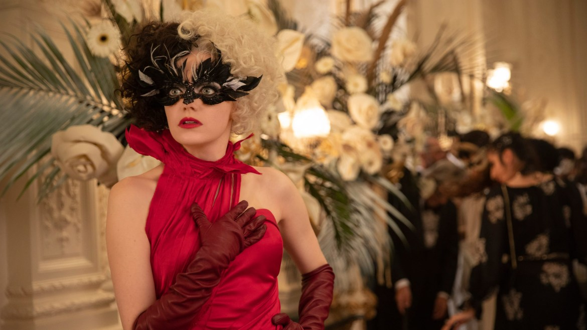 Emma Stone as Cruella posing in a red dress at a glamorous ball as seen in the new Disney live-action film.