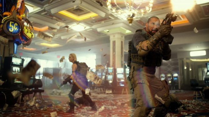 Dave Bautista and Nora Arnezeder shooting their way through a zombie-filled casino with money flying in the air as seen in Army of the Dead directed by Zack Snyder.