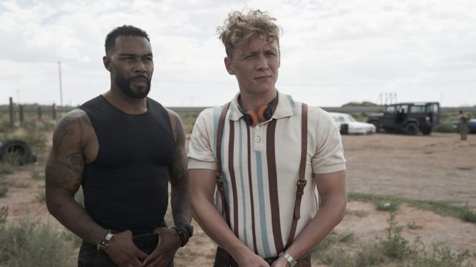 Omari Hardwick and Matthias Schweighöfer preparing for battle in a desert camp as seen in Army of the Dead directed by Zack Snyder.