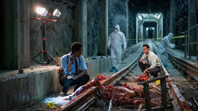 Chris Rock and Max Minghella investigating a gory subway crime scene filled with blood and guts as seen in Spiral: From the Book of Saw.