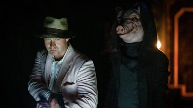 Daniel Petronijevic as a detective getting ambushed by the new Jigsaw killer in a pig mask as seen in Spiral: From the Book of Saw.