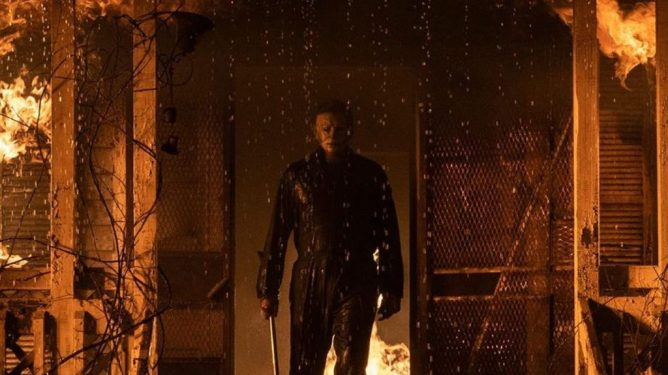 Michael Myers steps out of a burning house with a huge metal blade ready in hand as seen in HALLOWEEN KILLS produced by JASON BLUM.