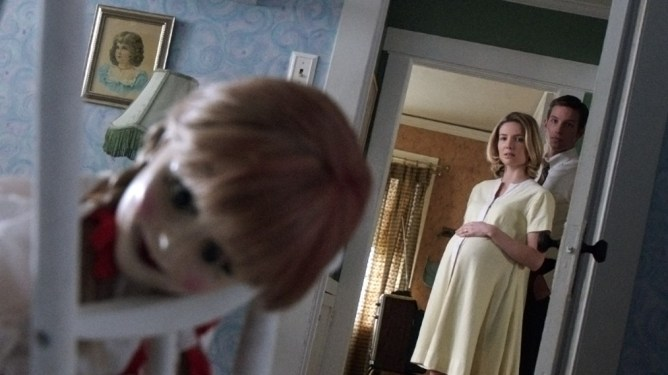 The demonic Annabelle doll in a baby's crib while a pregnant mother and father stare in fear in the back as seen in ANNABELLE, coming in at number 6 in our Conjuring Universe ranking.