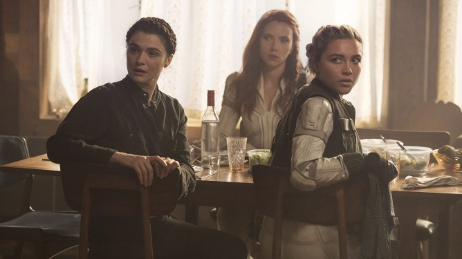 Rachel Weisz, Scarlett Johansson, & Florence Pugh sit at a dinner table while wearing spy costumes as seen in BLACK WIDOW, the latest MCU film to hit theaters.