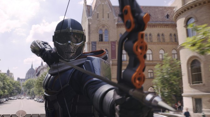 The MCU version of Taskmaster readies a bow and arrow similar to Hawkeye as seen in BLACK WIDOW, coming soon to theaters and Disney+.