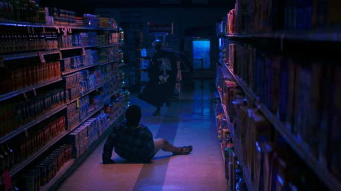 A killer in a skeleton costume chases down his latest victim in an empty and dark grocery store as seen in FEAR STREET PART 1: 1994 on Netflix.
