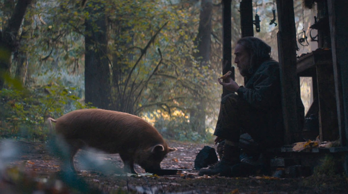 Nicolas Cage sits with his red pig while eating cooked truffles in the forest as seen in the new revenge drama PIG.