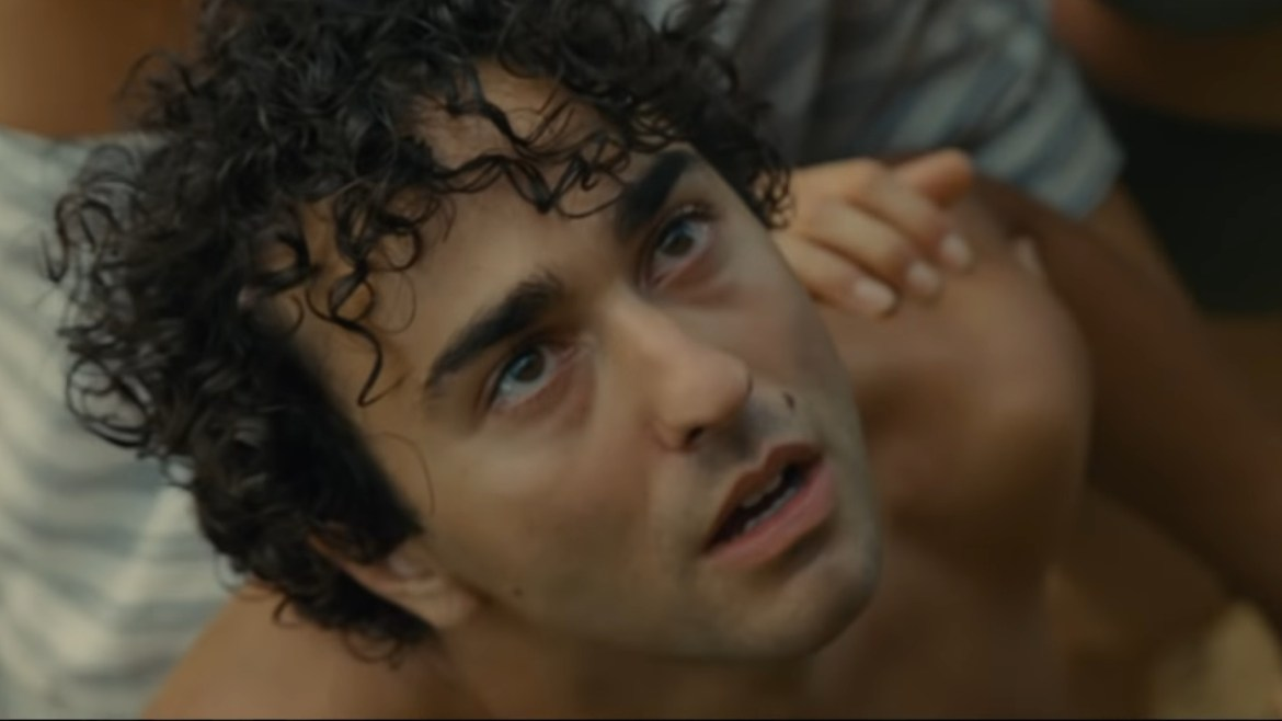 Alex Wolff looking to the sky with tears in his eyes as seen in the new M. Night Shyamalan Horror Thriller OLD.