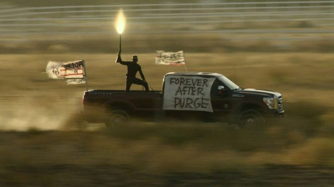 """A masked purger shooting a shotgun in the air while riding high speed on top of a truck that has a sign that reads """"Forever After Purge"""" as seen in the new horror movie THE FOREVER PURGE."""