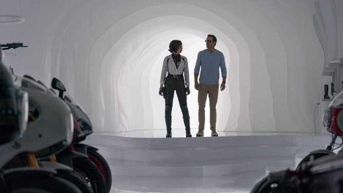 Jodie Comer as Molotov Girl and Ryan Reynolds as Guy enter a room filled with weapons and motorcycles through a white portal as seen in FREE GUY written by Matt Lieberman.