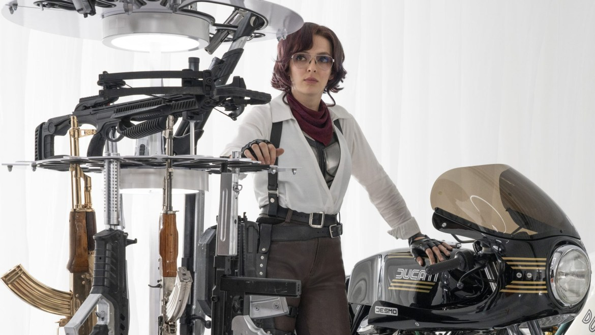 Jodie Comer as Molotov Girl next to a motorcycle and arsenal of vast machine guns as seen in the new video game action comedy FREE GUY.