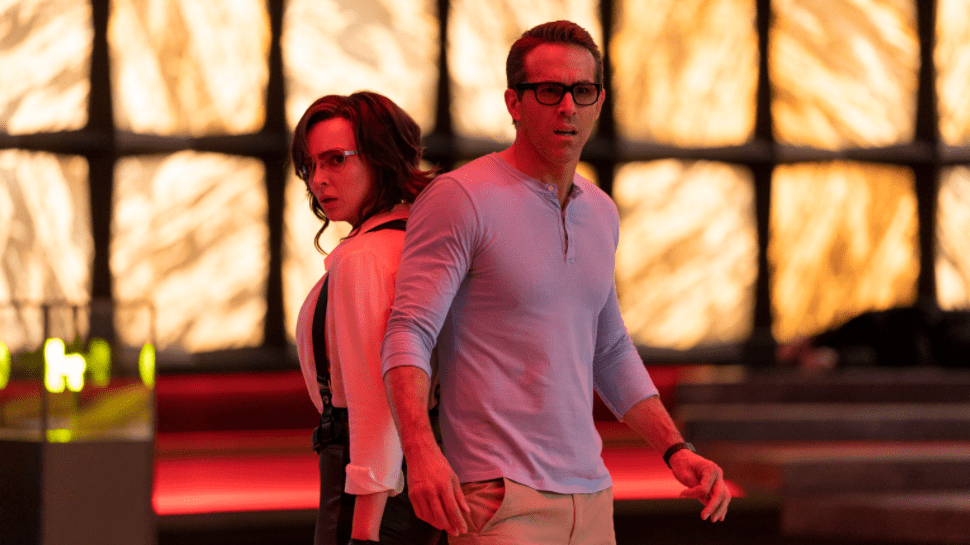 Ryan Reynolds as Guy and Jodie Comer as Molotov Girl posing back to back as seen in the new action video game comedy FREE GUY.