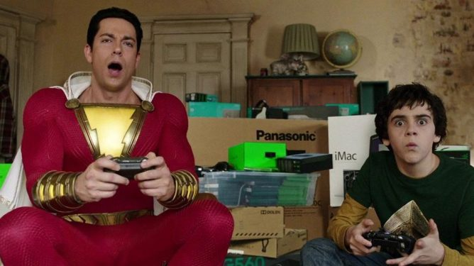 Zachary Levi as Shazam plays Xbox video games with his foster brother played by Jack Dylan Grazer as seen in SHAZAM!, coming in at number 2 in our DCEU ranking from worst to best.