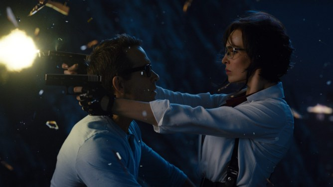 Ryan Reynolds as Guy sharing an intimate moment with Jodie Comer as Molotov Girl while she shoots guns sitting on his lap as seen in the new action comedy FREE GUY.