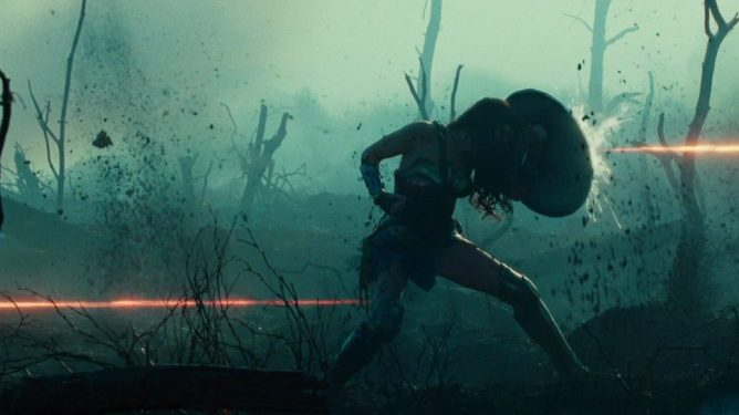 Gal Gadot as Wonder Woman holds off bullets with her shield in No Man's Land during WWI as seen in WONDER WOMAN, coming in at number 4 in our DCEU ranking from worst to best.