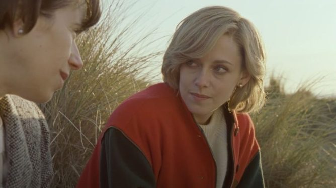 Kristen Stewart as Princess Diana sits in a field with a friend as seen in SPENCER directed by Pablo Larraín.
