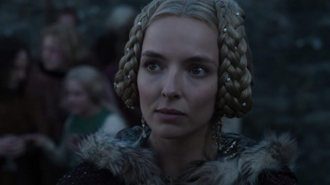 Jodie Comer sports braided blonde hair while wearing a winter coat in THE LAST DUEL directed by Ridley Scott.