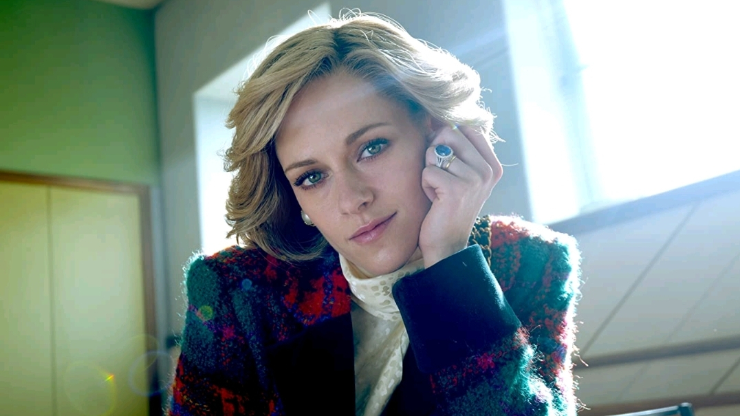 Kristen Stewart as Princess Diana tilting her head and starring into the camera as the sun shines on her face as seen in SPENCER directed by Pablo Larraín.