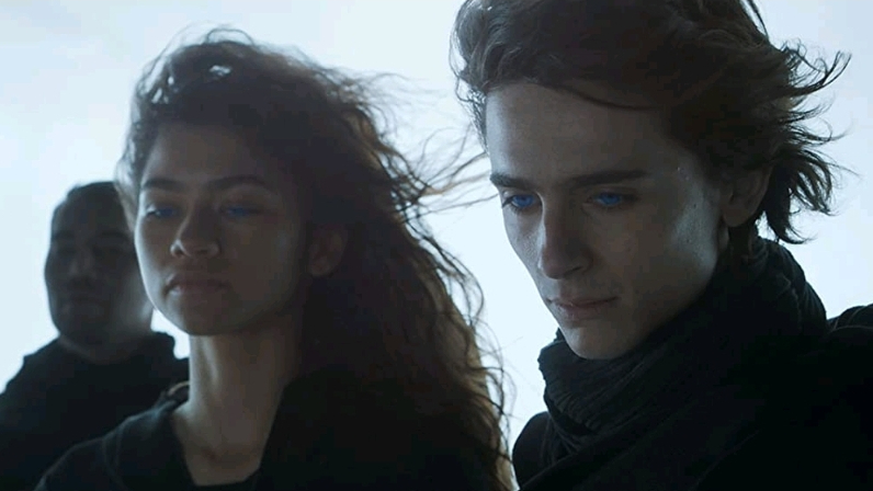 Zendaya and Timothée Chalamet stand together with their eyes glowing bright blue as seen in DUNE directed by Denis Villeneuve, coming to HBO Max in October 2021.