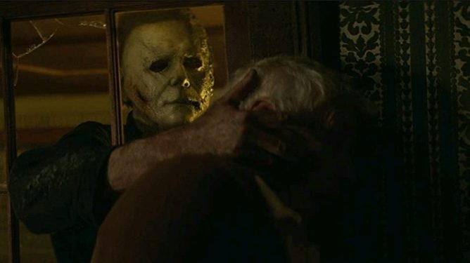 Michael Myers breaks through a glass window and grabs an elderly man from inside his home by the head as seen in HALLOWEEN KILLS.