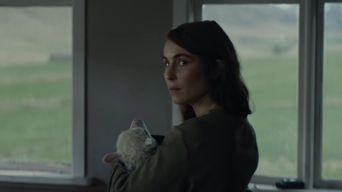 Noomi Rapace holds her adopted newborn half-human, half-sheep hybrid daughter Ada as seen in the latest A24 film LAMB.