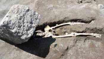 Ancient Roman fleeing Mount Vesuvius crushed by flying rock