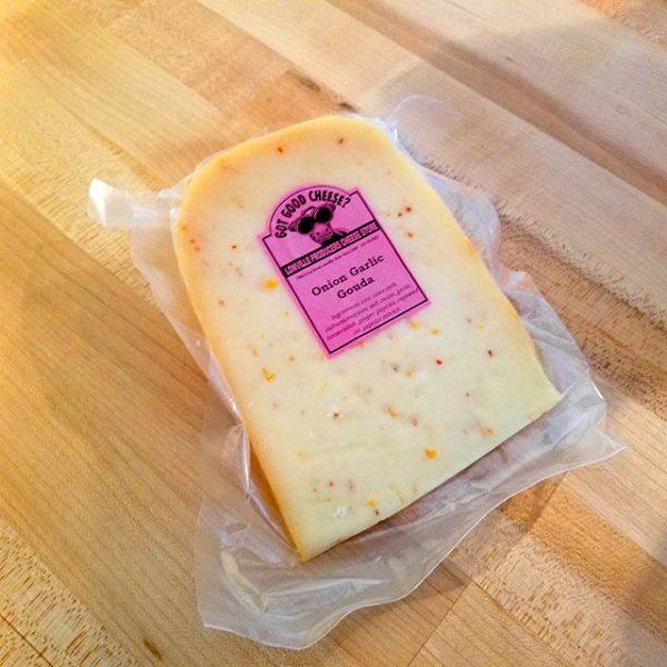 A wedge of Onion Garlic Gouda cheese.