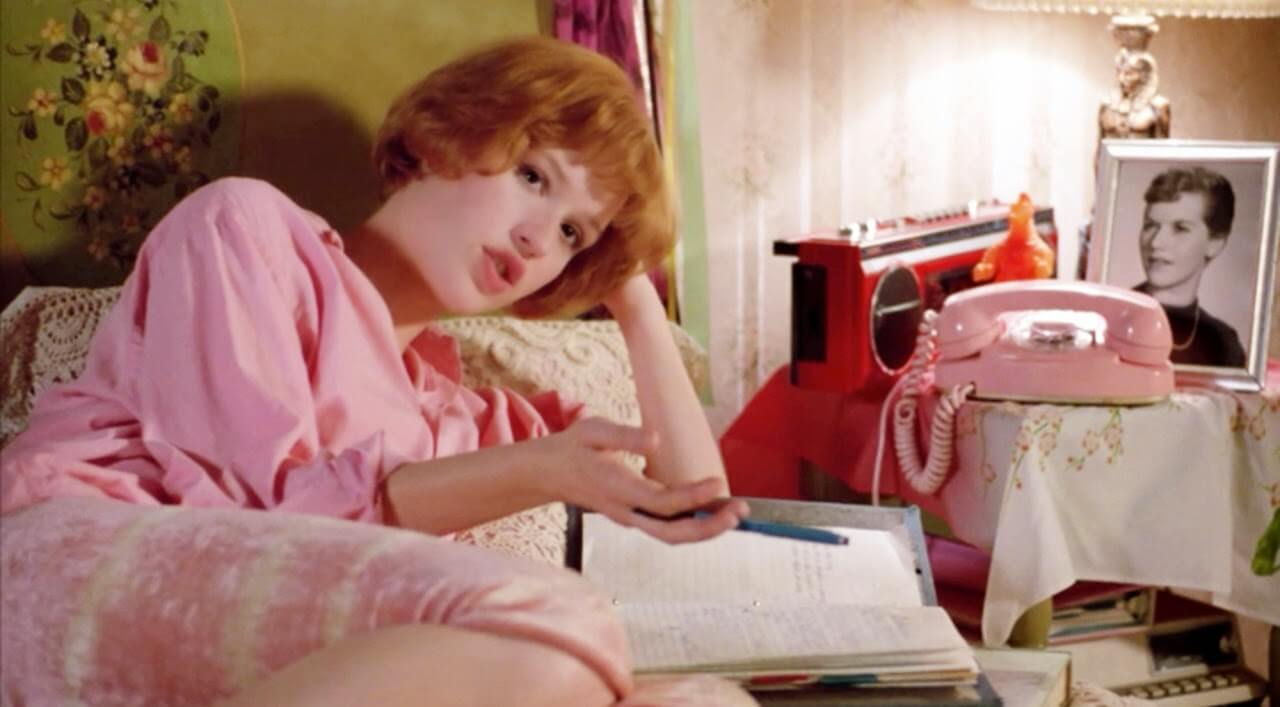 Molly Ringwald in a bed dressed all in pink in Pretty in Pink