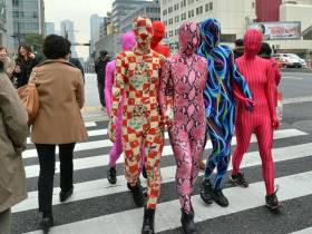 six people crossing a street in full spandex Zentai suits