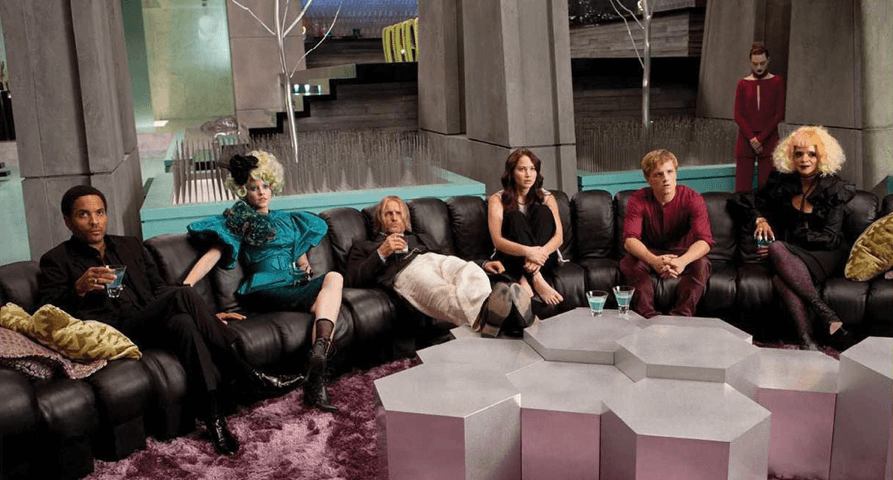 Main characters from Hunger Games sitting on a large couch