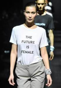 """White woman on runway wearing t-shirt that says """"The Future is Female,"""" inspired by protest signs"""